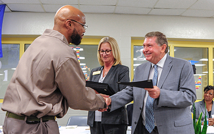 Pamlico Community College President Jim Ross presents certificate to Larry Burgess