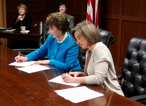 Hope Williams and Jennifer Haygood sign agreement.